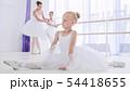 Child girl ballerina in white tutu is doing stretch exercises on ballet lesson. 54418655