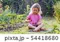 Little girl is eating strawberry and looking at camera sitting on the grass. 54418680