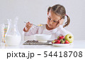 Bored little girl doesn't want to eat cornflakes with milk for breakfast. 54418708