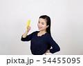 白い背景の前でセキセイインコと戯れている笑顔の若い女性 54455095