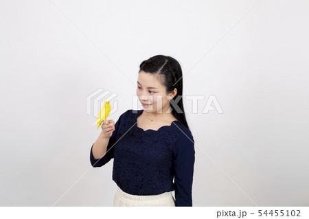白い背景の前でセキセイインコと戯れている笑顔の若い女性 54455102