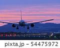 夕焼け空の中着陸態勢の旅客機 54475972