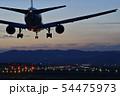 夕焼け空の中着陸態勢の旅客機 54475973