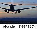 夕焼け空の中着陸態勢の旅客機 54475974