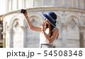 Young attractive woman stand under Pisa tower take a selfie and waving with her hand 54508348