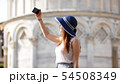 Young attractive woman stand under Pisa tower and take a selfie 54508349