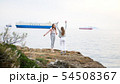 Two young attractive women dancing on the rocky shore 54508367