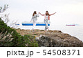 Two young women dancing on the rocky shore 54508371