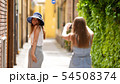 Two young women walking through the alleys - they take pictures of each other. 54508374