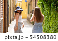 Two young women walking through the alleys - One of them posing for photo 54508380