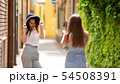Two young women walking through the alleys - One of them take a photo for other 54508391