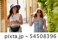 Two young smiling women walking through the alleys - One of them show to other something 54508396