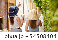 Two young women walking though the alleys - One of them show to other something 54508404