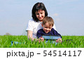 Mother and child spend time sitting on green grass and watching children's movie on tablet computer. 54514117
