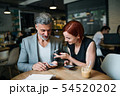 Man and woman having business meeting in a cafe, using smartphone. 54520202