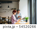 Man and woman having business meeting in a cafe, using laptop. 54520266
