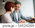 Man and woman having business meeting in a cafe, using laptop. 54520269