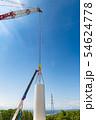 風力発電用風車の組み立て作業中のクレーン作業と送電鉄塔 54624778