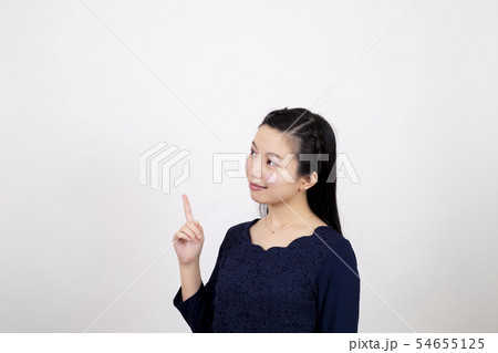 白い背景の前で右手の人差し指を上に向けている笑顔の若い女性 54655125