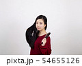 白い背景の前でブラシを左手に持って髪の毛を梳かしている若い女性 54655126