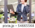オフィス背景でノートパソコンを持ちガッツポーズをする30代女性 54665568