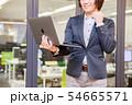 オフィス背景でノートパソコンを持ちガッツポーズをする30代女性 54665571