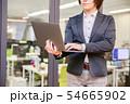 オフィス背景で立ってノートパソコンを入力する30代女性 54665902