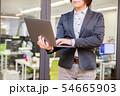 オフィス背景で立ってノートパソコンを入力する30代女性 54665903