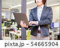 オフィス背景で立ってノートパソコンを入力する30代女性 54665904