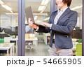 オフィス背景で立ってノートパソコンを入力する30代女性 54665905