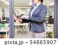 オフィス背景で立ってノートパソコンを入力する30代女性 54665907