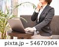 ソファに腰掛けノートパソコンを入力する30代女性悩むポーズ観葉植物背景 54670904