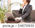 ソファに腰掛けノートパソコンを入力する30代女性観葉植物背景 54670930