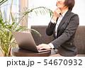 ソファに腰掛けノートパソコンを入力する30代女性観葉植物背景 54670932