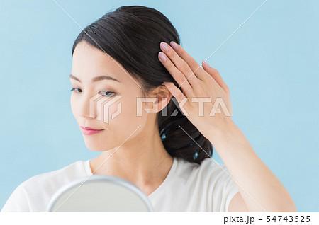ヘアチェックする女性(青背景) 54743525
