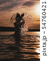 Young model swimming in the sea - sunset time. Attractive silhouette with spray 54760421