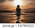 Young model swimming in the sea - sunset time. Attractive silhouette with spray 54760422