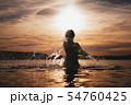 Young model swimming in the sea - sunset time. Attractive silhouette with spray 54760425