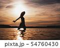 Happy Carefree Woman Enjoying Beautiful Sunset on the Beach 54760430