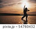 Happy Carefree Woman Enjoying Beautiful Sunset on the Beach 54760432