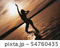 Happy Carefree Woman Enjoying Beautiful Sunset on the Beach 54760435