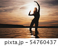 Happy Carefree Woman Enjoying Beautiful Sunset on the Beach 54760437