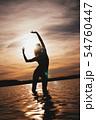 Happy Carefree Woman Enjoying Beautiful Sunset on the Beach 54760447