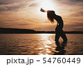 Happy Carefree Woman Enjoying Beautiful Sunset on the Beach 54760449