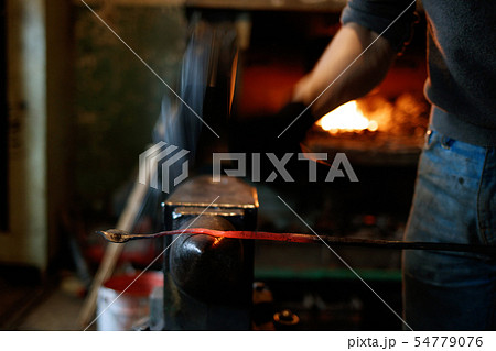 Blacksmith forging red-hot metal with hammer. 54779076