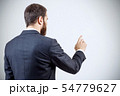Businessman pointing to something or touching by forefinger. 54779627