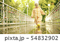 Funny little girl in orange waterproof raincoat and rubber rain boots walks on puddle after rain 54832902