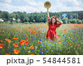 Lovely young romantic woman in straw hat on poppy flower field posing on background summer. Wearing 54844581
