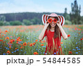 Beautiful young woman holding red poppies in front of her eyes and standing in flower meadow 54844585