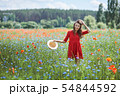 Lovely young romantic woman in straw hat on poppy flower field posing on background summer. Wearing 54844592